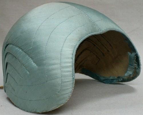 Hedemoramössa? i ljusblått sidentyg. Foder av naturvitt bomullstyg. Ett handvävt band av lin  i nacken.