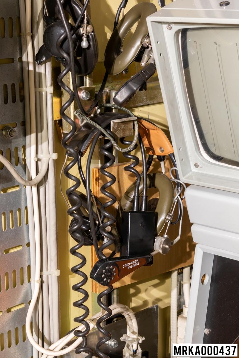 Huvudmikrotelefon för talsamband för operatörer i mätstation 727. Består av hörtelefon, mikrofon, S/M-omkopplare och spiralkabel. Huvudmikrotelefonen är ansluten till don på undersidan av anslutningslådan. Till samtliga huvudmikrotelefoner finns hållare.
