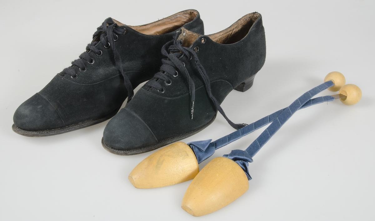 Av svart mocka. Lädersula. Läderklack med sula av gummi. Svart skoband. 7 par nitade hål. Klacken stämplad: GSA 1890. Viskafors. Skoblock av trä med metallskenor klädda med blått tyg.