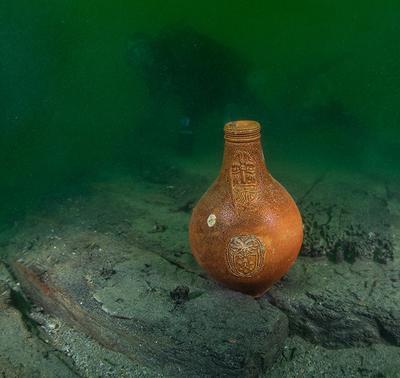 Bartmannskrukke i oransje keramikk, fra siste halvdel av 1600-tallet, står på bunnen blant båtdeler fra vraket av Pelikanen.