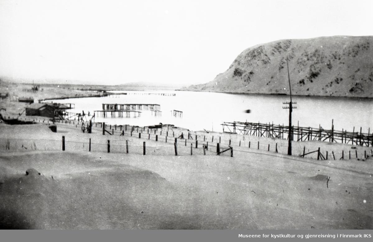 Deler av Nordvågen sett fra nord. Branntomter, noen brakker og fiskehjeller. I bakgrunnen Vestersida. 1945-46.