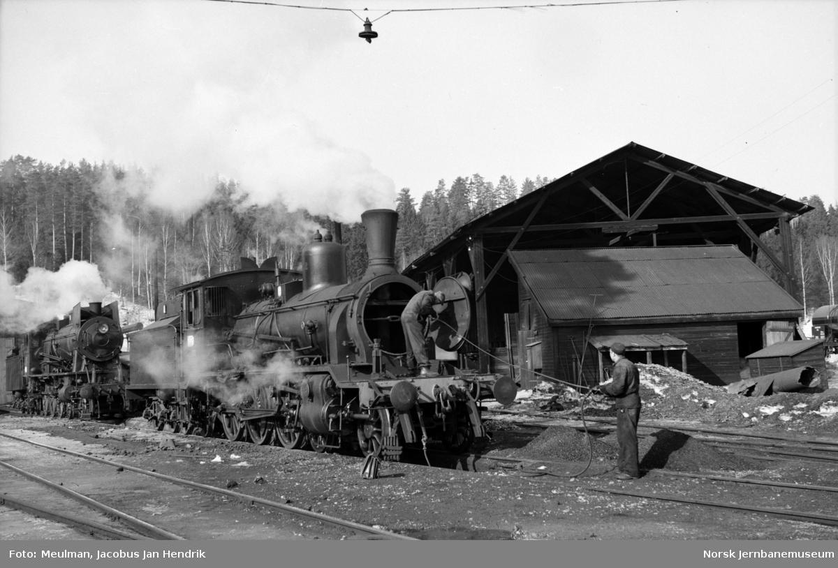 Damplokomotiv type 18c nr. 212, feiing av kjelrør ved lokomotivstallen på Hønefoss stasjon. I bakgrunnen et damplokomotiv type 30.