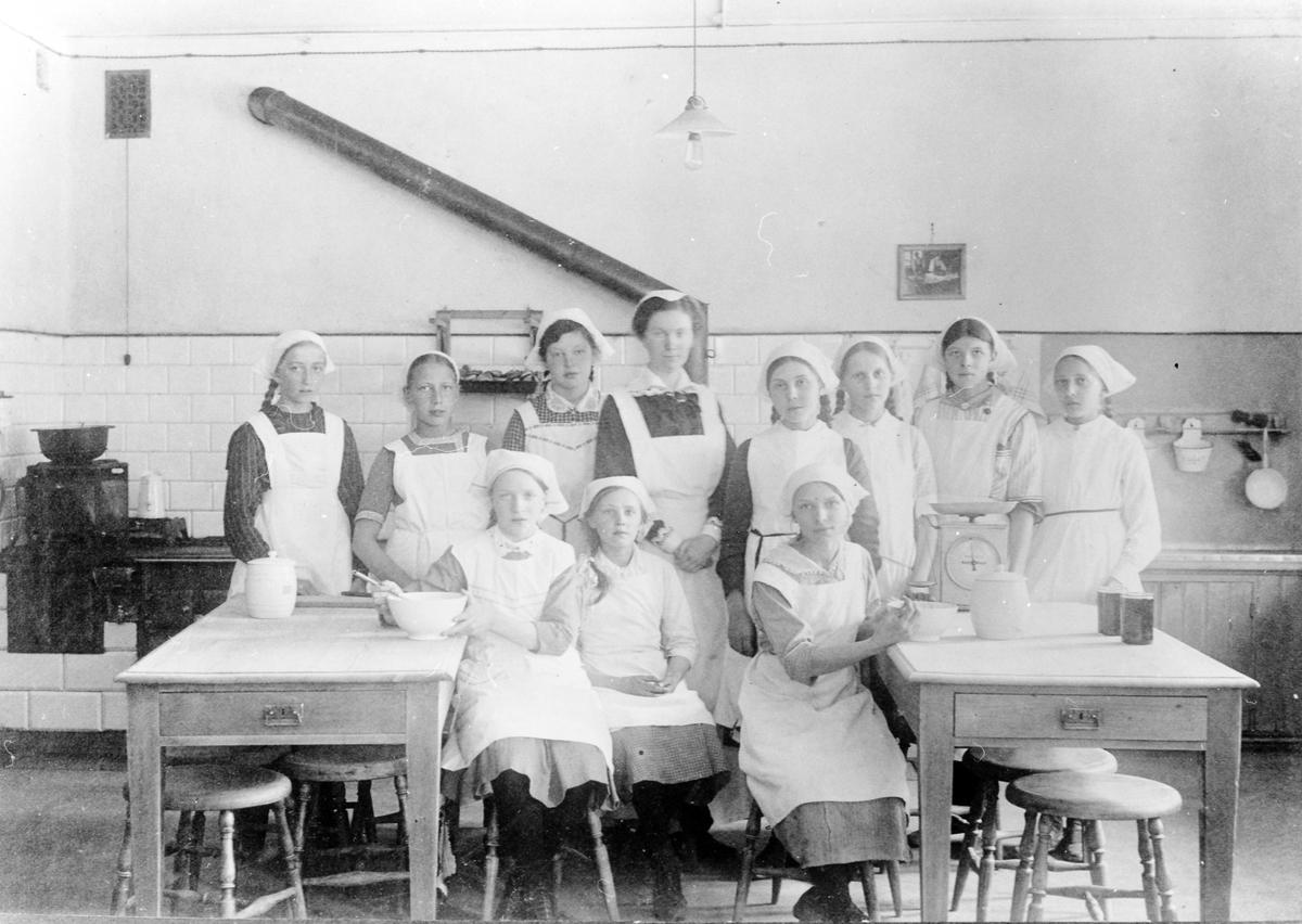 En lärarinna med en grupp flickor på en matlagningslektion i ett skolkök på okänd skola i Alingsås.