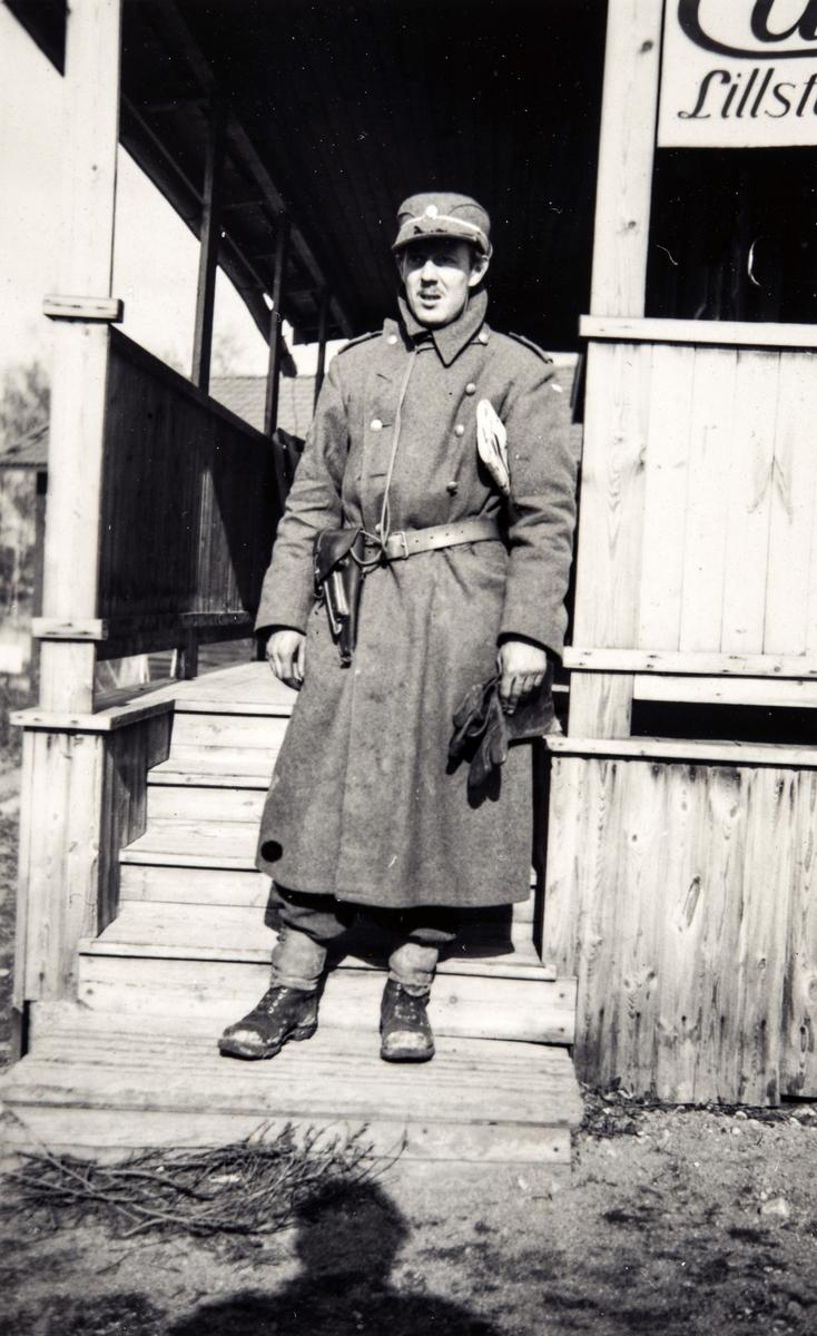 Portrettfotografi av en mann i uniform fremfor en bygning i Manøver, Helsingland under 2. verdenskrig.