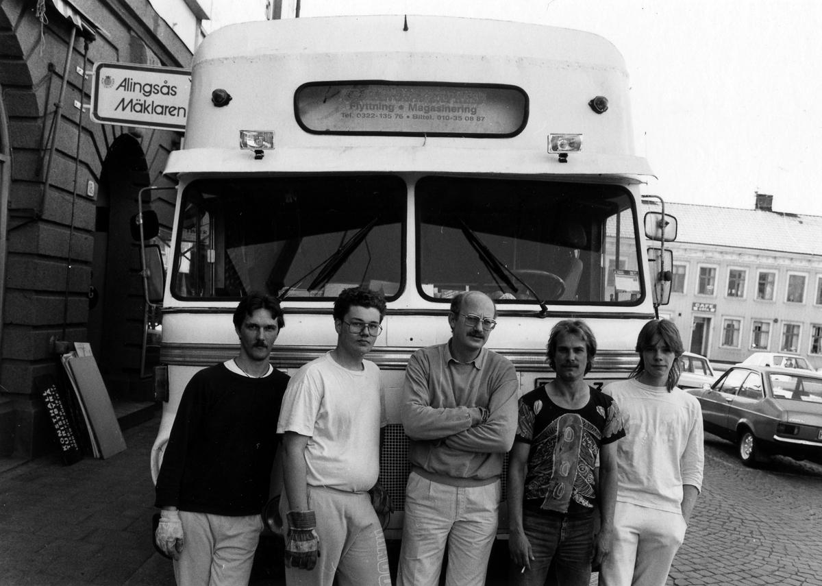"""5 män lutar sig mot framsidan av en flyttbil från Alingsås Express. Till vänster, på husväggen, en skylt med text """"Alingsås Mäklaren"""". Bilden tagen på Nygatan utanför Palladium i samband med att museets expition flyttade dit."""