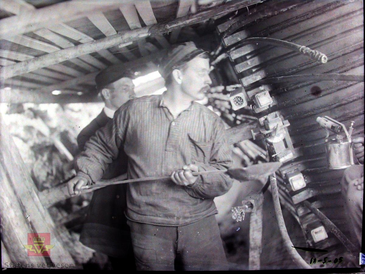 Gamle Gulsvik hengebru under bygging 1905. Brua har en  total lengde på 97 meter. Bygd i perioden 1903-1906 av Kværner Brug i Oslo. Inngikk som del av Hallingdalvegen fram til 1971 da vegen ble lagt om og ny bru bygd ved siden av. Da den ble bygd var dette Skandinavias lengste hengebru. Den er et tidlig eksempel på hengebru i Norge og er derfor tatt med i Nasjonal verneplan for veger, bruer og vegrelaterte kulturminner. Fredet ett § 22a i kulturminneloven i 2008. Rehabilitert med utskifting av tredekke og maling av stålkonstruksjoner i 2010.  Bildet viser fortinning av kabelender. Tinn smeltes ved hjelp av feltesse og blåselampe.