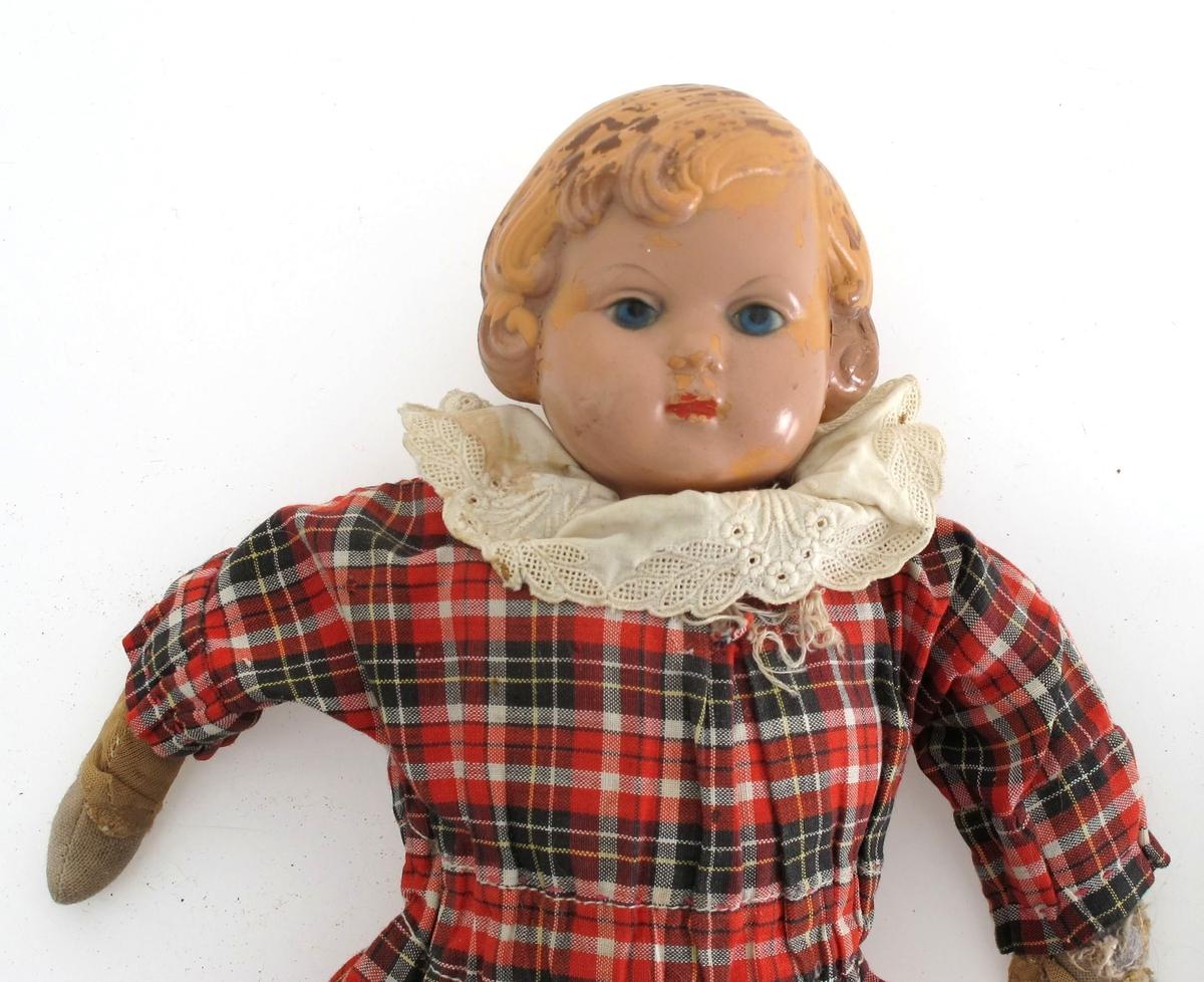Tøydukke med støpt hode i plast. påsydd en filledukke. Kjole av rutet bomullstoff, med blondekrage. Undertøy. Trykknapper i kjolen.