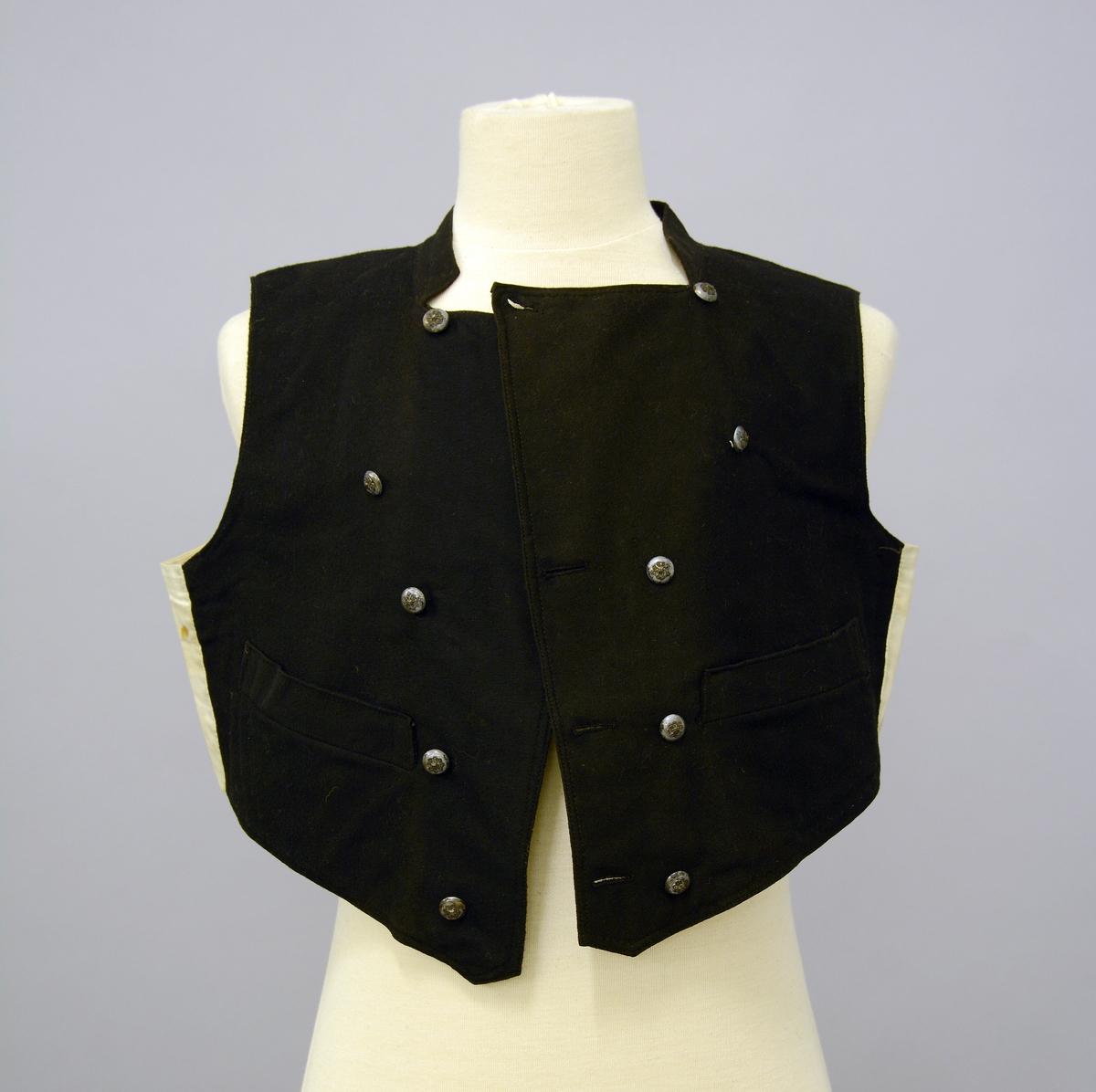 Grøntrøyekledning (A-E) B.Vest av svart klæde, med kvit bul; dubbelspent med 5 skaaleknappar med roset påå, i sylv. Fra Protokoll.