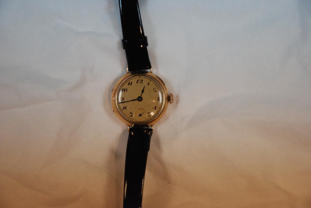 En gullklokke med sort lerreim. Reima er skiftet ut, men selve uret er original. Trolig produsert mellom 1925 og 1940. Ingen stempler eller andre id. merker.