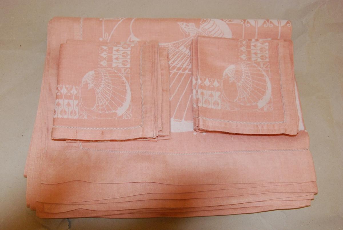 Gammelrosa damaskduk med 12 tilhørende servietter. Hvitt påfuglmønster. Produksjonsdato ukjent. I utmerket stand.