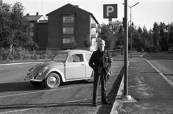 En man (Bexell) står invid en Volkswagen Bubbla på parkering