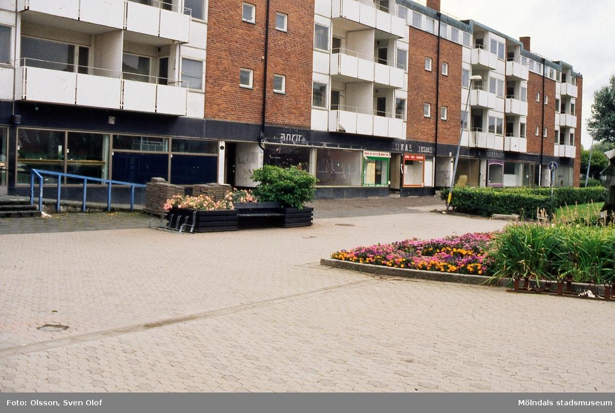 Bostadshus med affärslokaler i gatuplanet vid Jungfruplatsen i Mölndal, augusti 1999. Både affärer, lägenheter och post är tomma. Fastighetsägaren förhandlade med kommunen om att hyra ut till servicelägenheter, men det blev inget av detta. Lokalerna byggdes om till lägenheter.