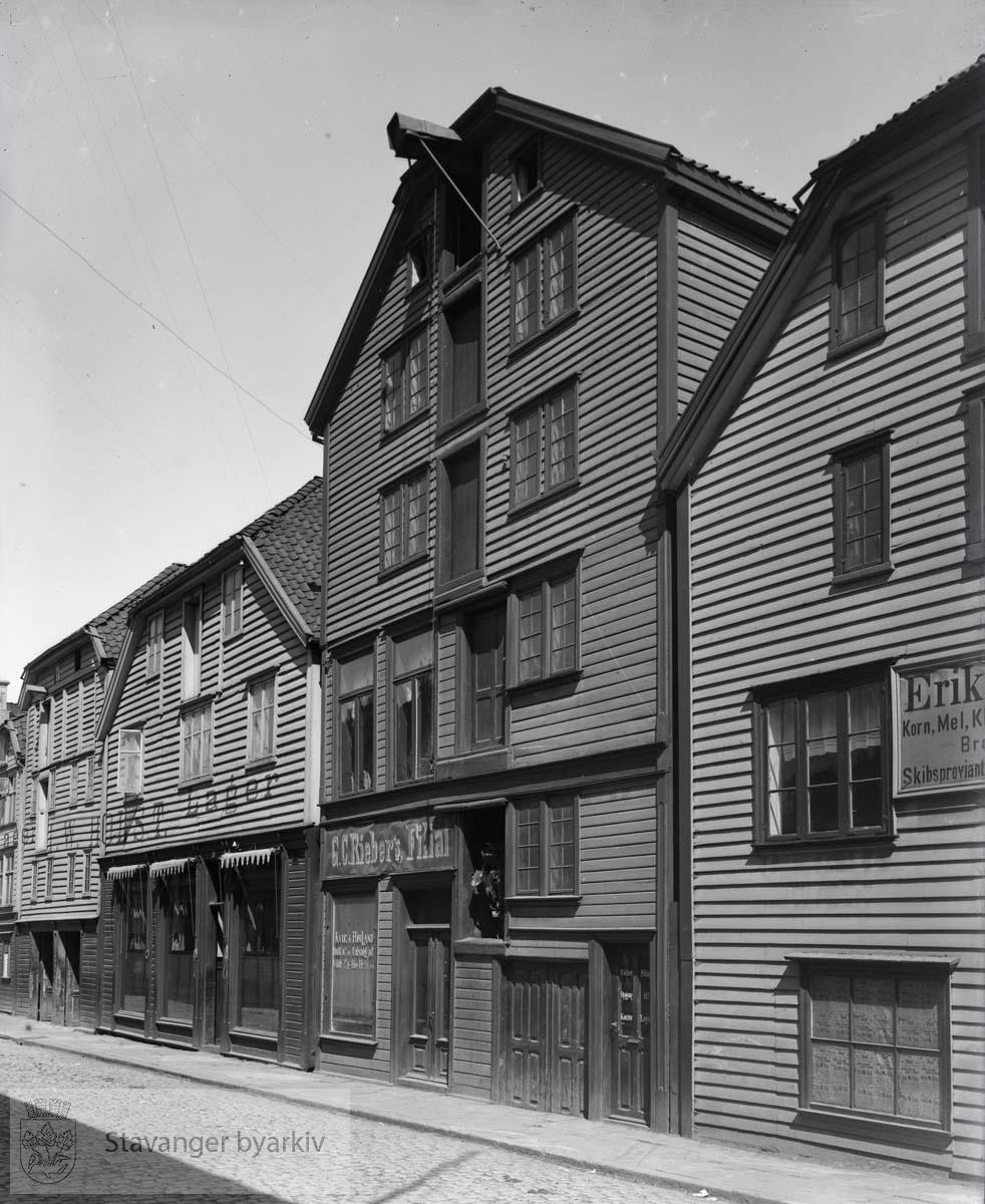 Til høyre: Kirkegata 48. Bygningene ble oppført etter brannen i 1860, da Nedre Holmegate ble anlagt. De ble bygget som sjøhus mot Børevigå med forretningslokaler mot Nedre Holmegate. De ble eid av grossister i korn og mel. G.C. Riebers filial i nr. 22 og J. W. Holsts lager i nr. 20.
