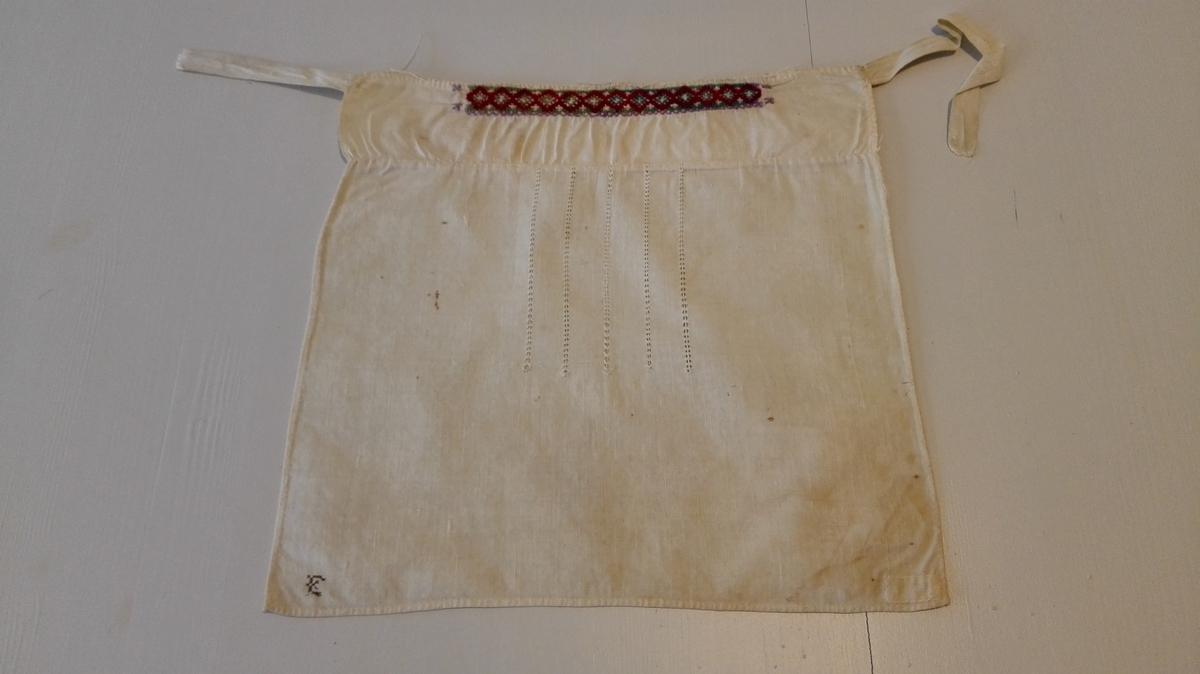 2 hylliker (11913 - 14).  11913 - Hyllik 31,5 x 31 cm. Har överst en bord sydd i kulört - violet, grön og rödbrun - uldtraad samt efter midten 5 striper uttrækssöm. I nedre venstre hjörne sydd med sort silke E.  Kjöpt av Brita Øvrebø, Ortnevik.