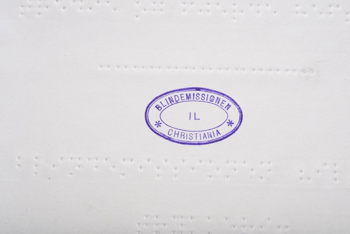 Notebok med noter i punktskrift. Ensidig trykk. Brunt marmorert omslag. Halvbind av svart tekstil. Turkis lapp med punktskrift er limt på forsiden av omslaget.