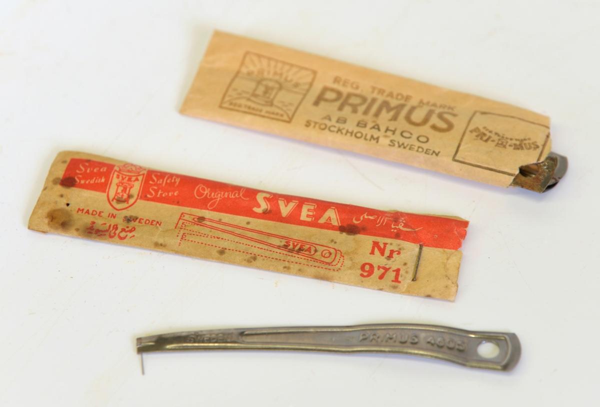A: Papplåda sammanhållen med papperstape med texten AB Bacho Stockholm Sweden och Primus Regd Trademark. Stor etikett med produktens namn och en bild på ett brinnande Primuskök mot solnedgång. Produktinformation på många olika språk. I etikettens övre högra hörn sitter en röd lapp som talar om att förpackningen innehåller Primus säkerhetskanna.    B: Själva köket. Höjd 220 mm, diam 210 mm. Två ringar över en brännare. Behållare för rödsprit. Namnet Primus  återfinns över hela köket. Etikett i snöre finns också.  C: Kanna för rödsprit. Primus säkerhetskanna.  D: Pappersförpackning, 80 mm lång. Text: Svea Swedish Safety stove Original Svea Nr 971. Innehåller tre stycken rensnålar för rensning av brännaren.  E: Pappersförpackning 115 mm lång. Text: Reg Trademark Primus AB Bacho Stockholm Sweden No 4605. Innehåller tre stycken rensnålar av märket Primus och en av märket Svea.  Från Arne Ekströms Handelsmuseum.  Modell: Primus No 5