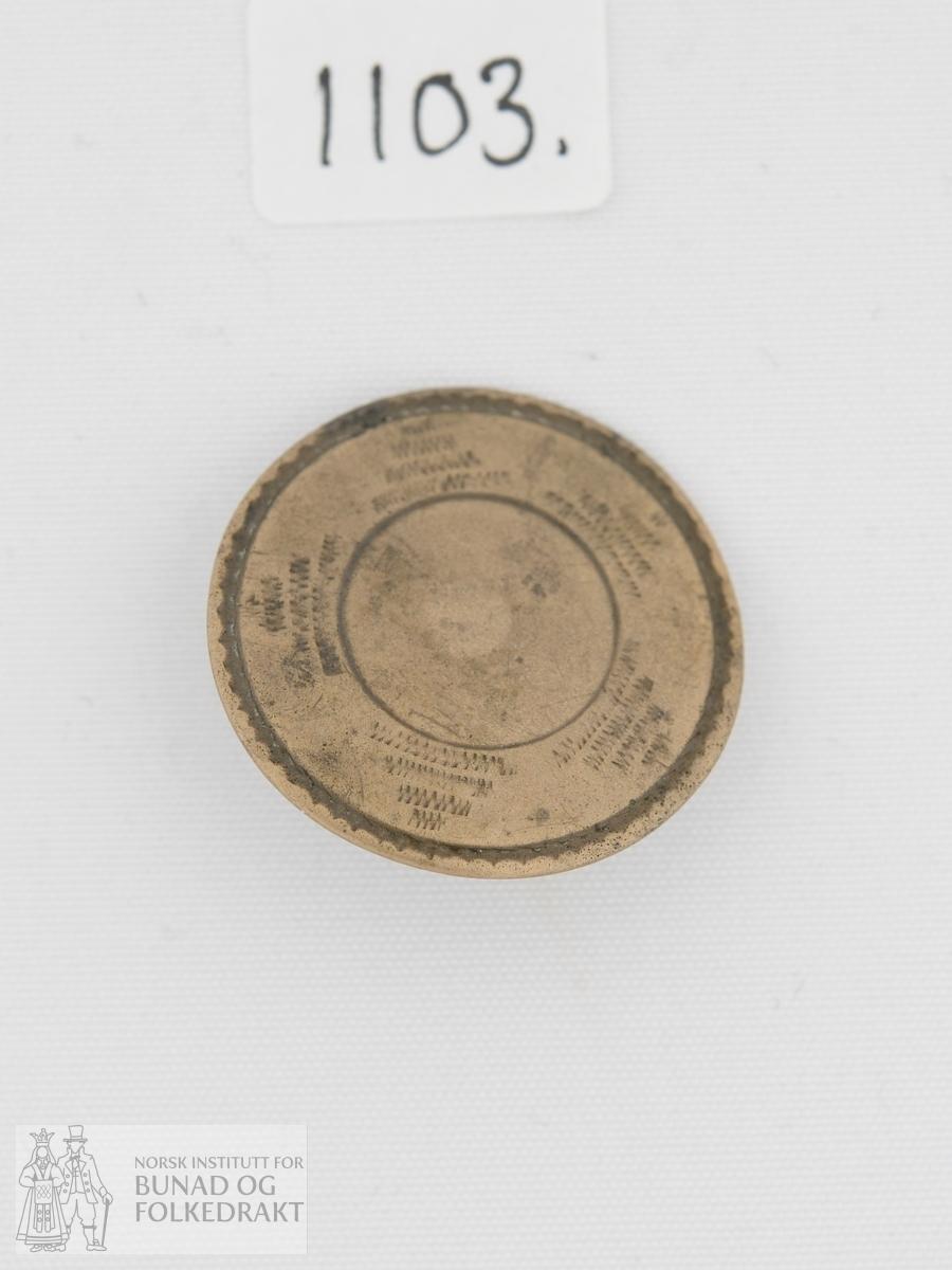 Knapp stansa ut av ei messingplate og pålodda krok på baksida. Knappen har prydnad i form av eit prega mønster med form som ei sol eller stjerne.