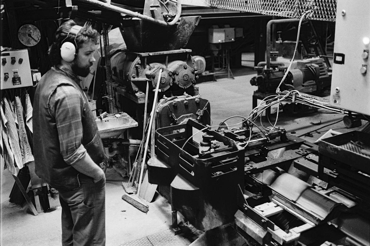 Sättare Tommy Hellbom övervakar tillverkningen av enkupigt taktegel i maskinhallen, Vittinge Tegelbruks AB, Vittinge socken, Uppland 1986