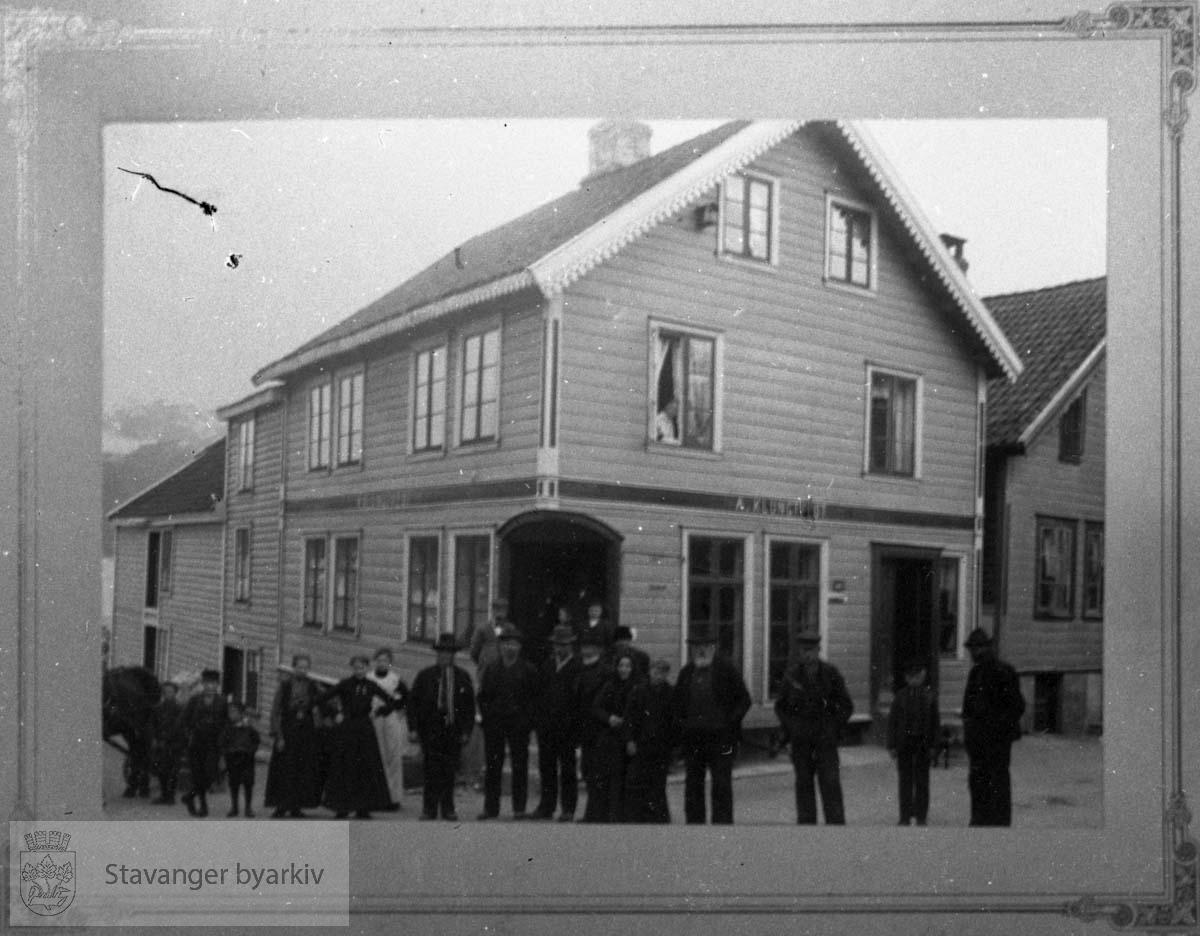 På huset i bakgrunnen står det A. Klungtvedt. Søstrene Klungtvedt drev et pensjonat i Nordbøgata 8 rundt forrige århundreskifte, men det ser ikke ut til å være dette huset...Avfotografert positiv