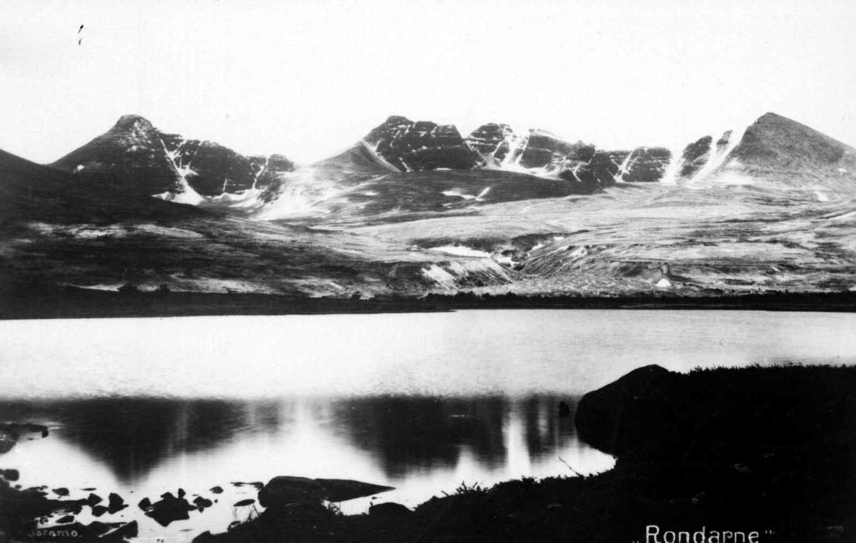 Repro etter postkort av Hans H. Joramo: Rondane med Neverbutjønnet foran og fra venstre, Høgronden Midtronden og Digerronden bak.