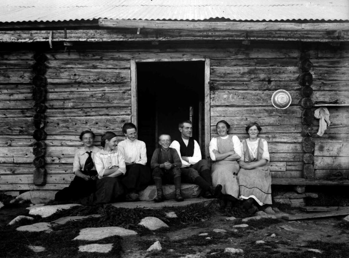 Ei gruppe personer utenfor Dokklia sæter, Gausdal, Vestfjell. Vaskvannsfat henger på veggen.