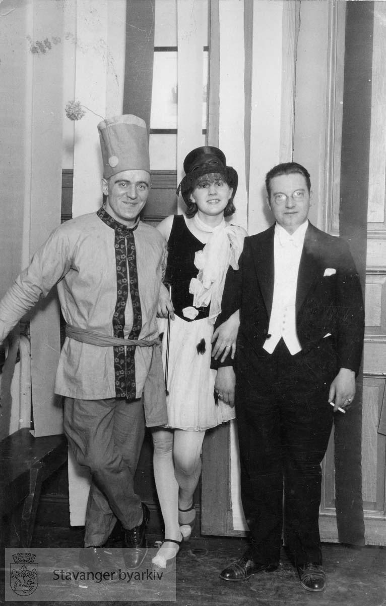 To menn og en kvinne i kostyme under kostymeball