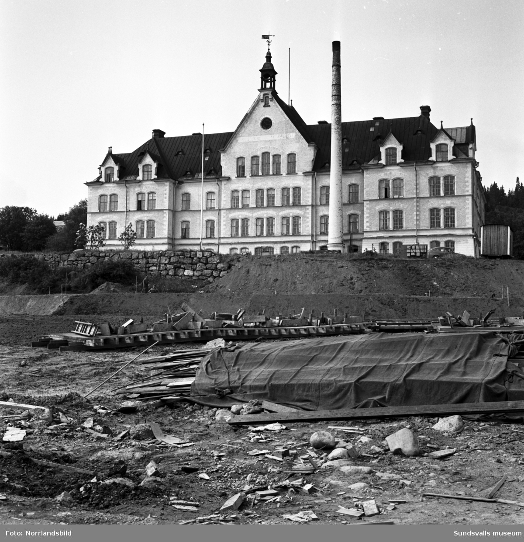Exteriörbilder av Birstahemmet, Sköns försörjningshem, ett par år innan det rivs. I förgrunden pågår markplanering för industriområdets utbredning.