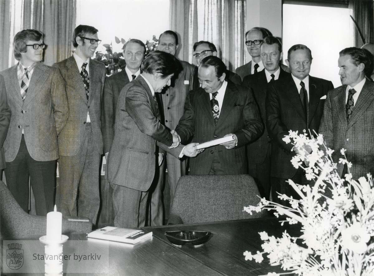 Ordførerer Arne Rettedal mottar et eksemplar av Kjølv Egeland. .Bakerst, nr. 2 fra venstre: Hans Eyvind Ness, ytterst til høyre: Journalist Per Barkved..Nr. 2 fra høyre: sosialrådmann Torgils Vaage.Nr. 4 fra høyre: Lektor Kristian Sunde