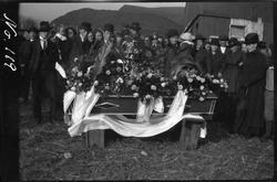 Blomsterprydet båre på et gårdstun, begravelsesfølget står b