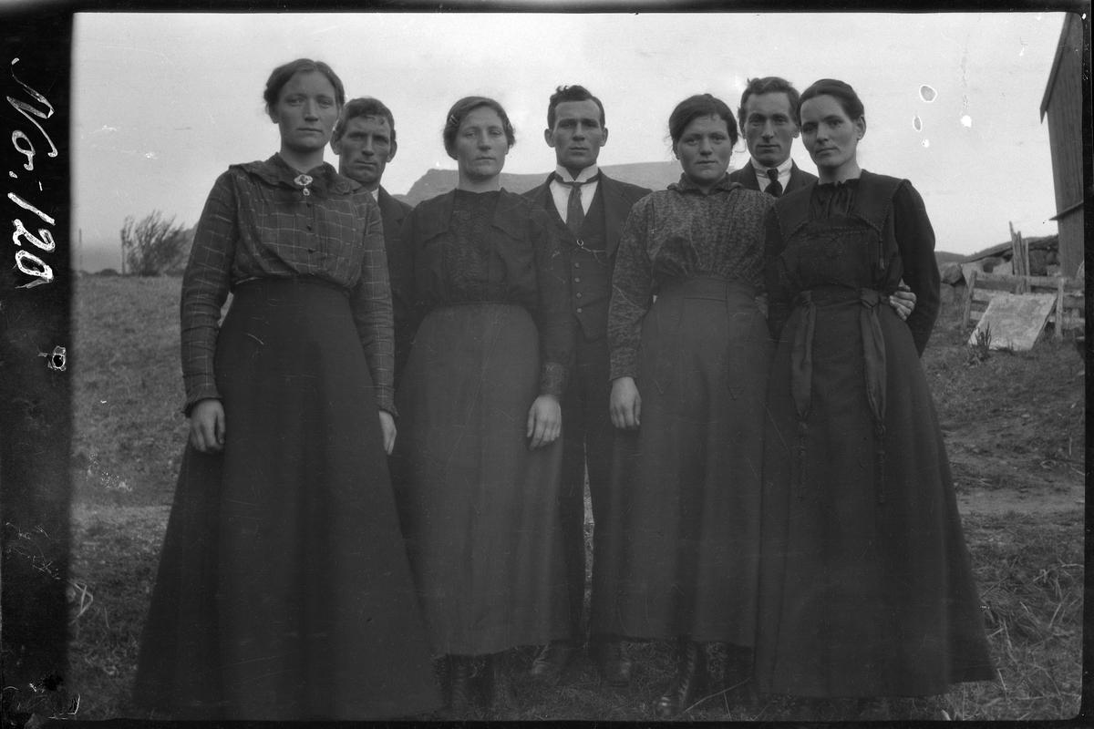 Gruppeportrett av syv personer stående på gårdstun.
