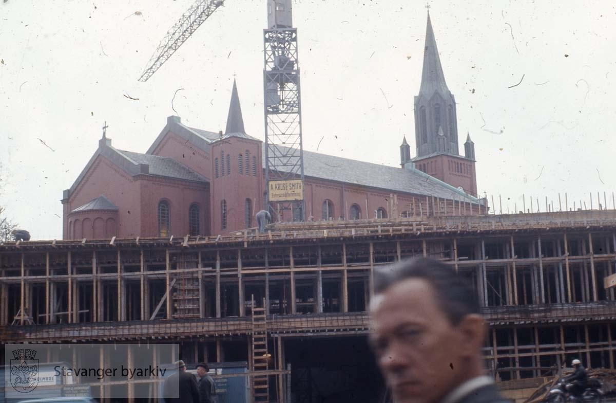 Misjonsbygget mot St. Petri.Mistroisk person foran kameralinsa.
