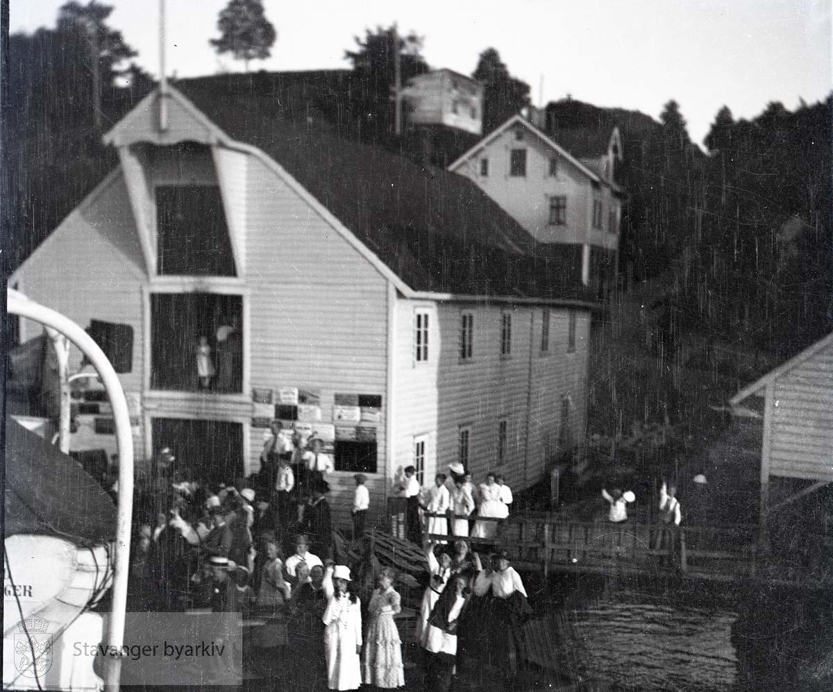 Forsamling på kai ved sjøhus