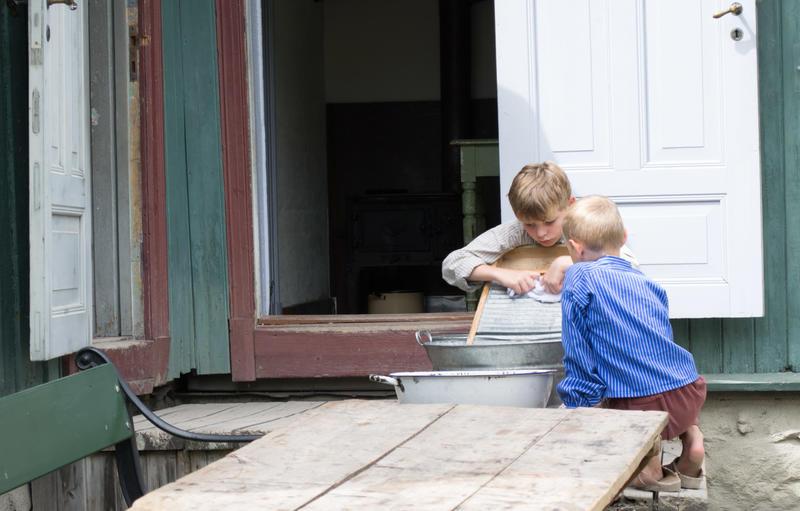 To gutter som vasker tøy på Enerhaugen i Gamlebyen på Norsk Folkemuseum.