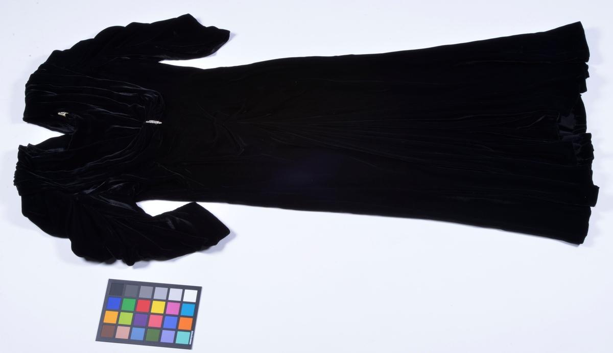 """Av svart sammet. Draperat framstycke. Dekorerat med strassmycke. Knäpps i ryggen med 17 knappar. Halvlånga ärmar. Etikett inuti klänningen, """"E S Ester Svensson Syateljé Alingsås, Tel: 400""""."""