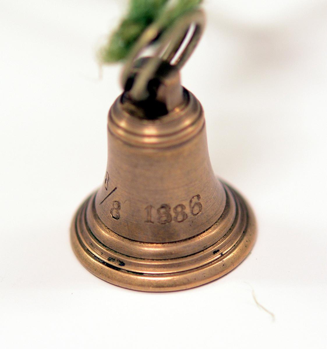 Signet av bronse, med initialene H.I. i dekorativ inngravering og ring rundt, støpt av Skiens gamle kirkeklokker, i klokkeform med feste på toppen og ring i. Medfølgende notat fra giveren til museet.