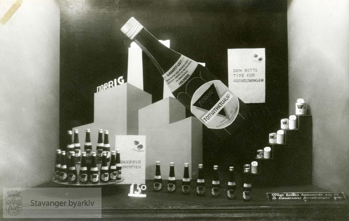 Utført av E. Jørgensen..Farver: Kongeblå sidevegger. Sort bakvegg og bunn. Kongeblå og lyseblå fabrikk med lys grønne skorsteiner og hvit røyk. Den store flasken i tomatfarge. ..Montert den 9. mars 1933. Momentant virkning.