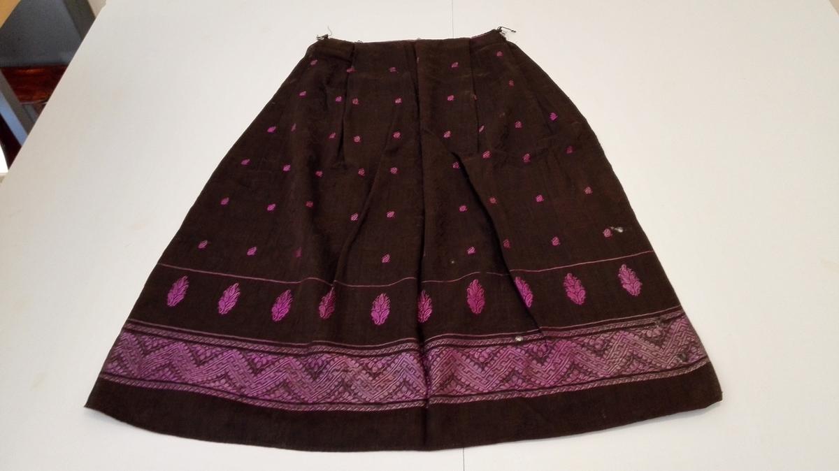 Rektangulært med to legg i kvar side. Bord i lilla silke nede og små knoppmotiv strødd symmetrisk over heile forkleet.