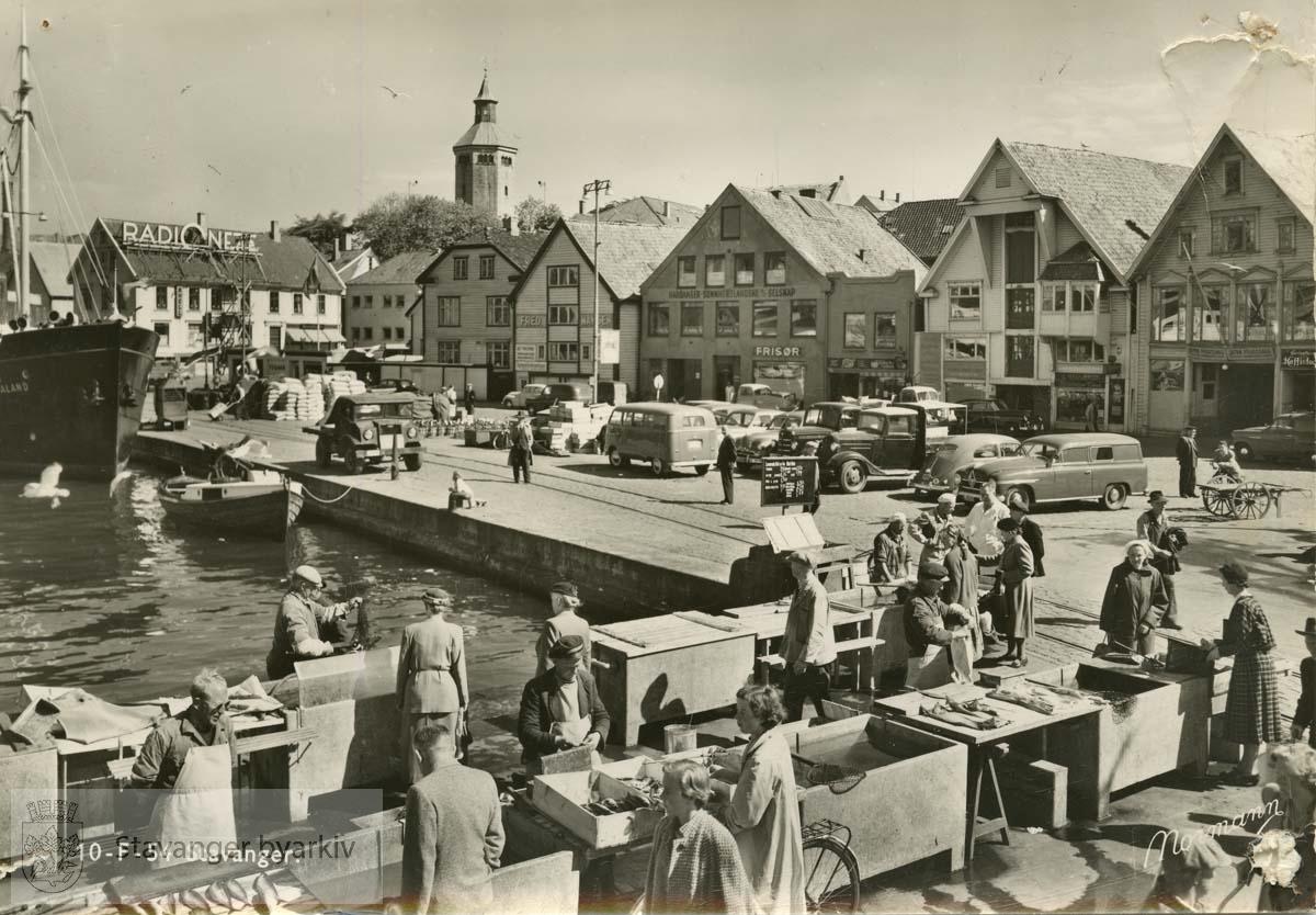 Fisketorget mot Skagen.Sjøhusrekka til høyre.Handel på fisketorget i forgrunnen.Valbergtårnet i bakgrunnen..