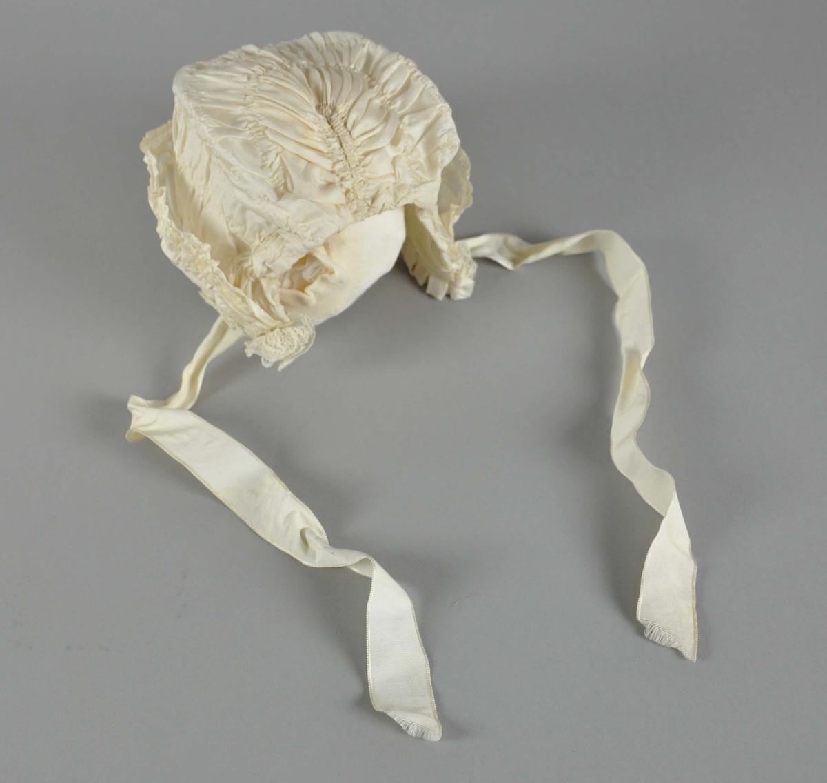 Hvit dåpslue med foldelagt stoff og blonder. Luen har påsydde knyttebånd ved sidene.