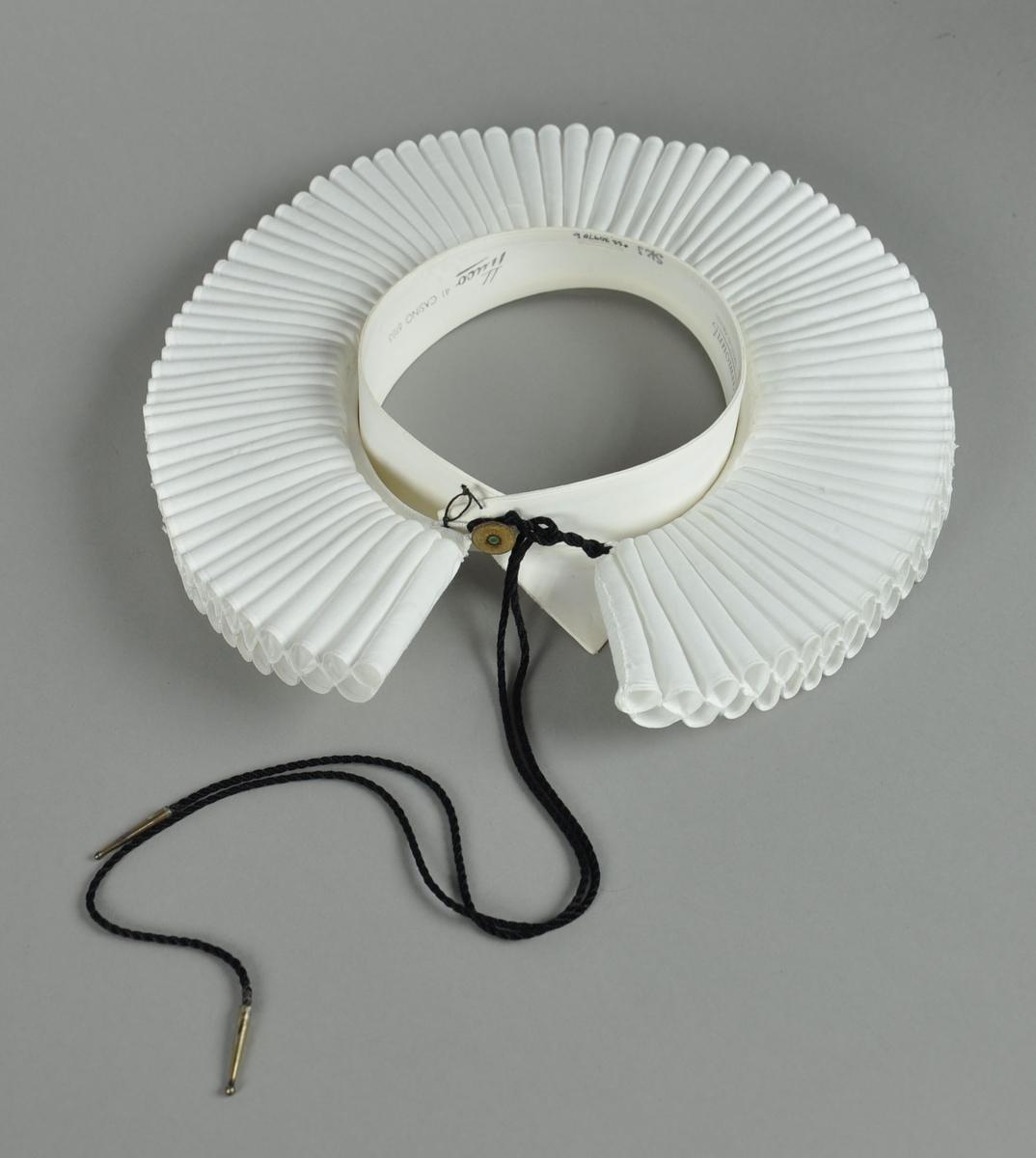 Hvit prestekrage av bomull. Kragen har 2 x 89 piper, 6,5 cm lange. Pipene et sammenfoldet bendelbånd med to hemper og svart messingtupper. Sammen med kragen hører en snipp, også hvit.