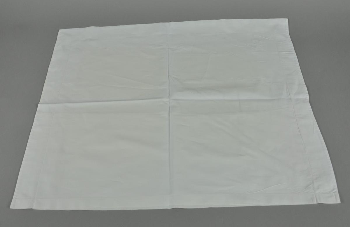 Hvitt putevar med brodert H. Det er noen hull i tekstilen.