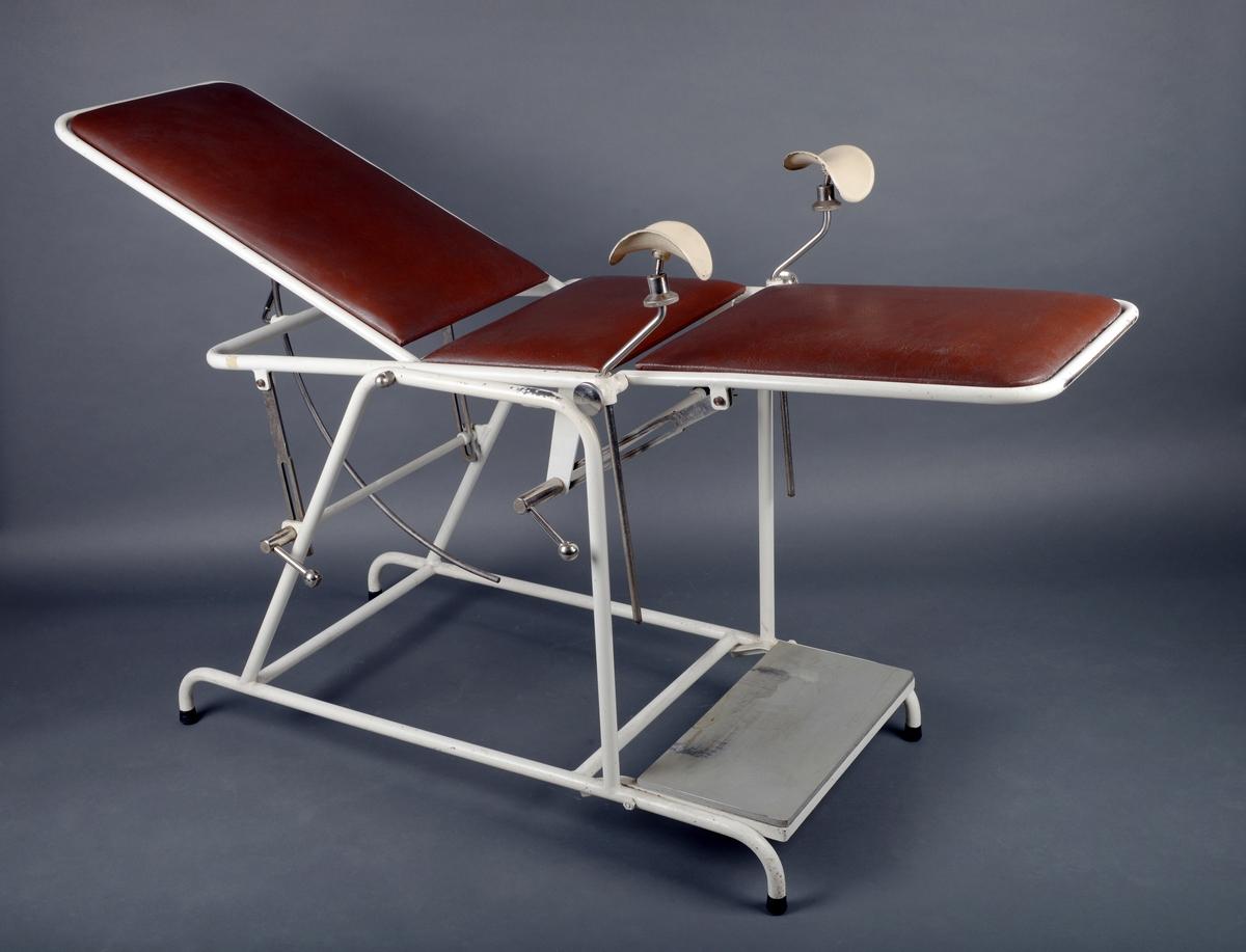 """Undersøkelsesbenk/gynekologisk benk av lakkert metall med todelt sete og hel rygg trukket med rødbrun skai. Skaien er stiftet fast til kryssfinerplater. Både sete og rygg er justerbare. Ryggen er justerbar ved hjelp av en bøyd metallstang med håndtak- når man løsner på håndtaket kan ryggen justeres opp og ned. På den ene langsiden er det håndtak/spaker som gjør at 1. hele stolen kan vippes fram og tilbake og 2. den fremste delen av setet (der man har beina) kan justeres opp og ned. Ved setet er det på hver side montert """"skåler"""" på dreibare stenger. Ved en gynekologisk undersøkelse legger man beina opp i disse skålene. Benken er montert på et understell av hvitlakkert metall. Den står på fire korte bein med svarte gummiknotter på. Foran på stolen er det montert på en gråmalt treplate (kryssfiner) som fungerer som et fotbrett/trappetrinn til hjelp når man skal opp i stolen."""