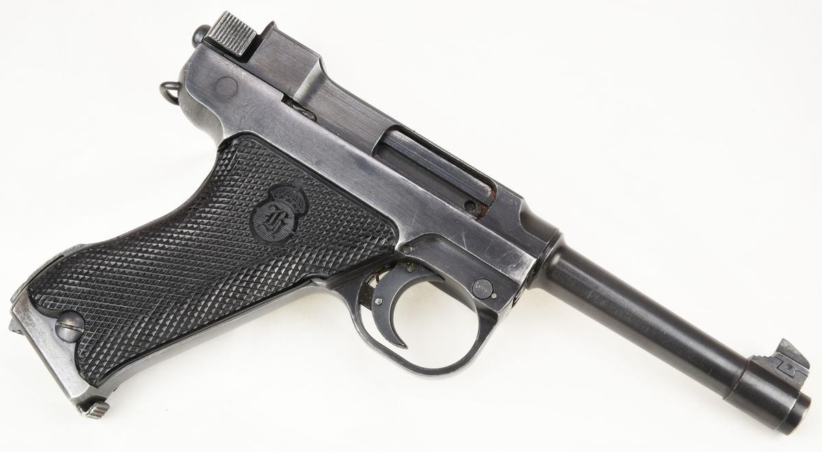 Pistol m/40 med hölster och tillbehör.  M/40 (:1) är en halvautomatisk pistol av kaliber 9mm som rymmer åtta patroner i magasinet. Pistolen är helt gjord i metall bortsett från greppytorna på pistolkolven som består av mönstrade bakelitplattor som också bär på Husqvarnas logotyp. Pistolen är oskadliggjord och går inte att använda.  Pistolen förvaras i sitt bruna original hölster (:2) av grisskinn som har plats för två magasin, en rengörningsstav samt ett kombinationsverktyg. Hölstret har beslag samt knappar gjorda i mässing. I hölstret förvaras ett reservmagasin (:3), en rengörningsstav i metall (:4) och ett kombinationsverktyg i pressad plåt (:5).