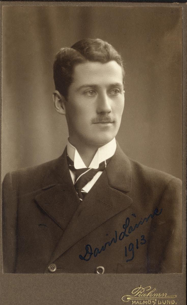 3c67a41ab92c Porträttfoto av en ung man i mörk kostym med stärkkrage och randig slips.  Nederst till