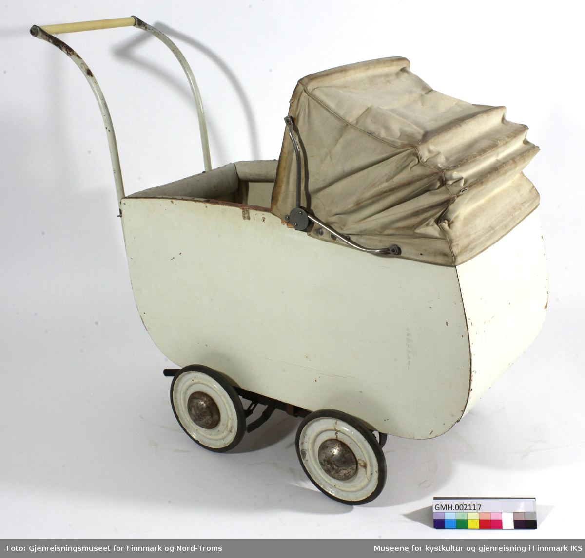 Barnevogna har en liggedel av tre og er malt hvit. Kalesjen er laget i hvit/beige kunstskinn. Liggedelen består av et treramme som er polstret og utkledd med hvit kunstskinn. Bunnen er av tre. Understellet er av metall og har en bremsehendel nede. Selve håndtaket er av plast i gul farge.