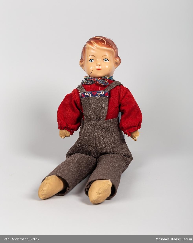 En docka som kallades Pelle. Dockan är från början av 1950-talet. Rolf som bodde på en lantgård utanför Trelleborg fick dockan när han var cirka 3-5 år. Dockans kläder är handsydda av hans moster Elsa som var född 1921.