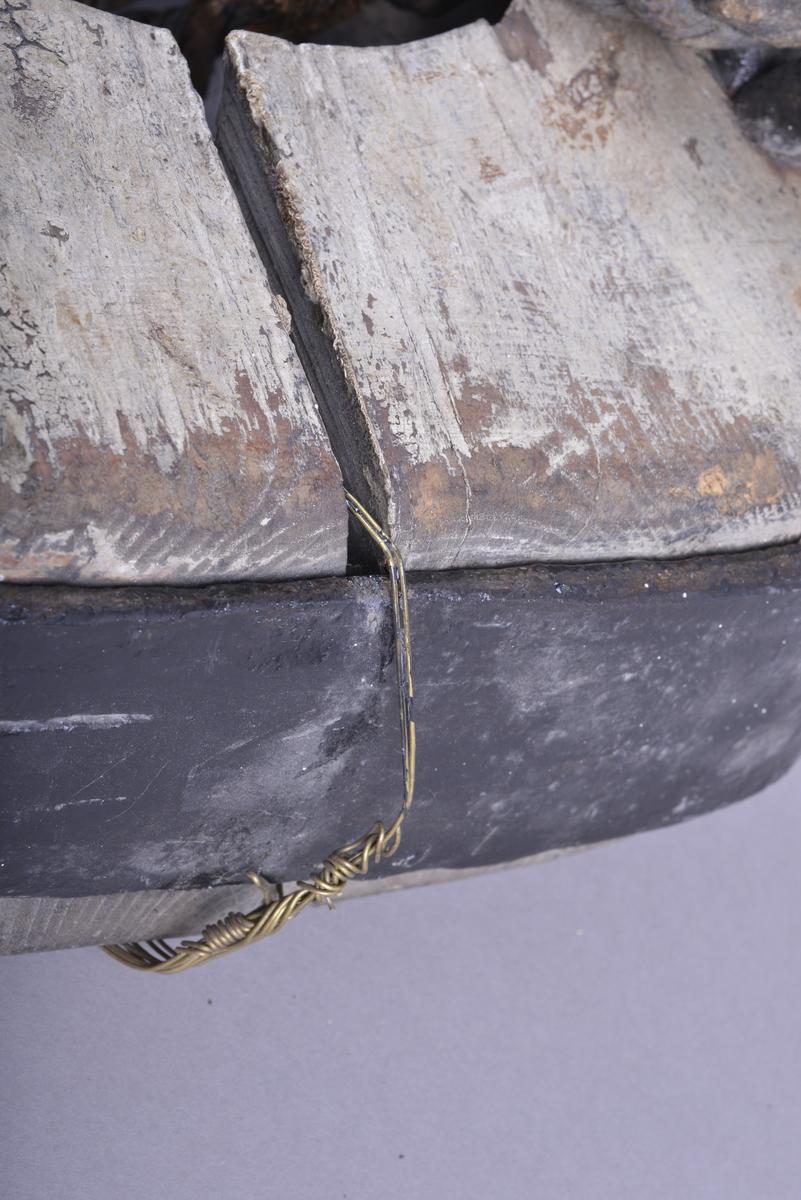 Beslag av treverk og jern. Treverket er avlangt, med jernbeslag langs hele ytterkanten. Beslaget har kraftige fester til øyebolter for feste av taljer på skip. Treverket har to store åpninger i midten, et firkantet og et rundt.  Treverket ser ut til å ha vært tidligere behandlet med beis eller maling. Det meste er slitt bort.