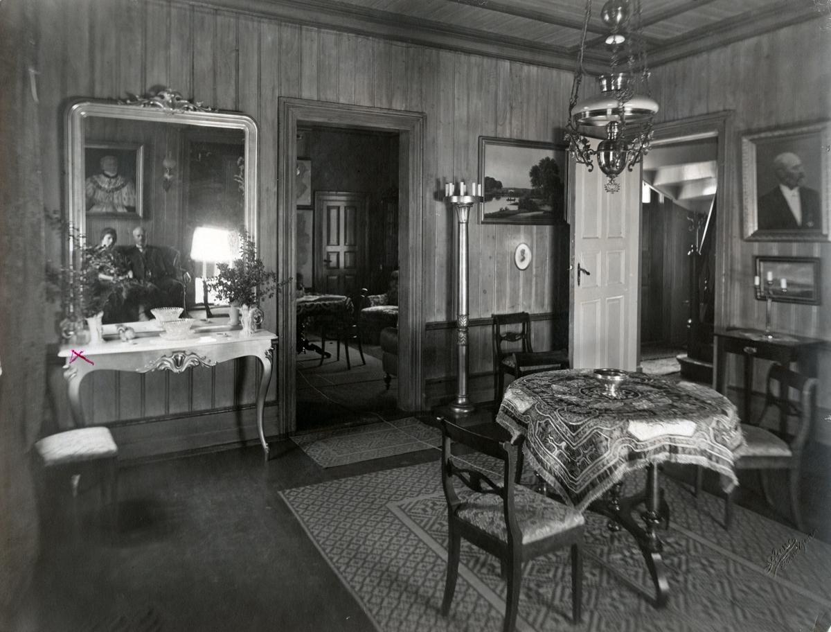 Bildet viser inngangshallen i 1. etasje, med åpne dører inn til Bachkes arbeidsværelse og inn til trappehuset til høyre. I speilet vises Victoria og Christian Anker Bachke.