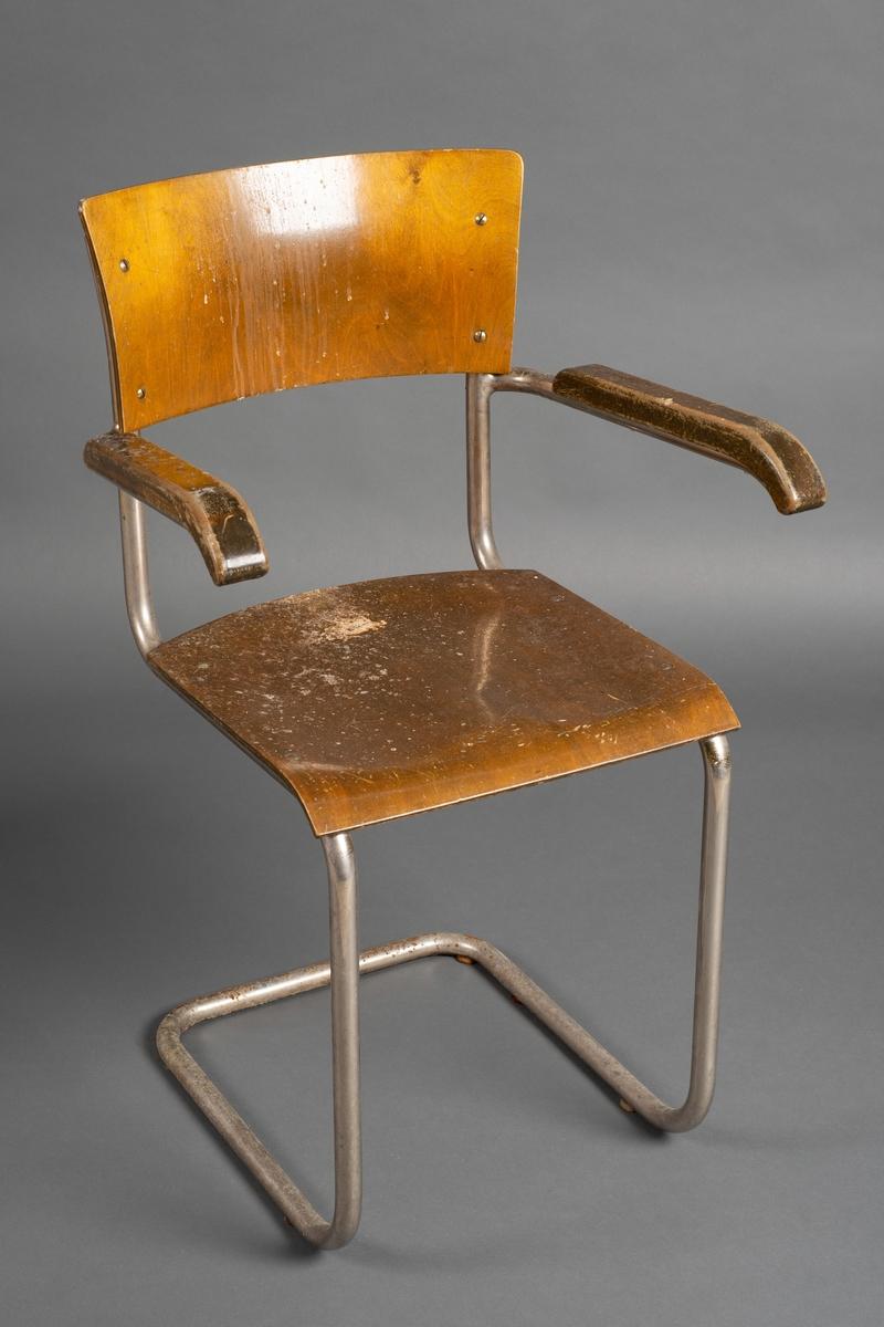 Stålrørstol med armlener, pasientstol. Stålrørskjelett med rygg og sete i kryssfiner, tre på armlener. Rygg, sete og armlener festet til stålrørskjelett med skruer.