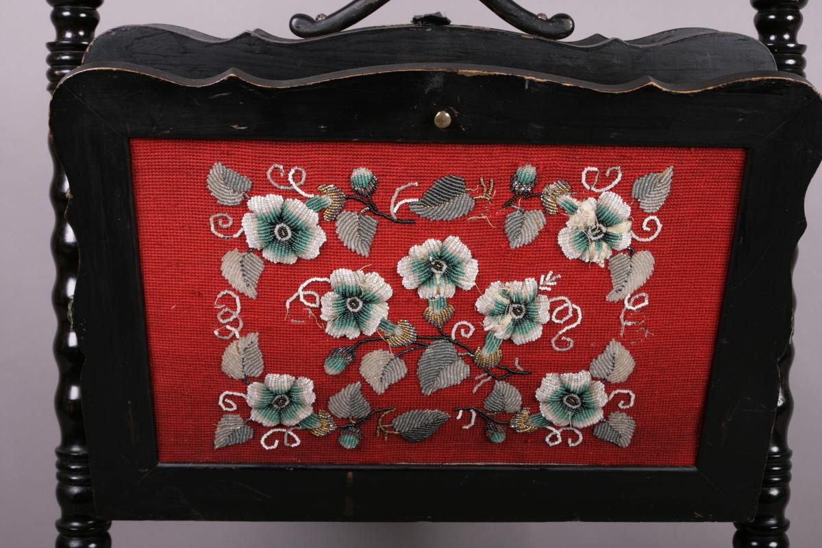 Stativ for oppbevaring av noter. Svartmalt treverk, dreide ben. Dekor på forside med rødt underlag i stoff dekorert med perler i blomstermønster. Baksiden dekorert på hvitt underlag med perler i blomstermønster. På toppen en kneppe som holder holderen samlet, kan åpnes som en vifte. Fire ulike deler kan åpne seg, slik at notene kan sorteres. Håndtak på toppen slik at noteholderen enklet kan flyttes rundt.